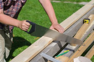 såg -sawing-long-wooden-plank-outdoors